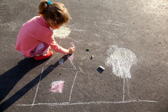 Girl draws painting sun house chalk on asphalt royalty free stock photography