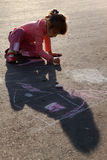Girl draws painting sun house chalk on asphalt Royalty Free Stock Photos