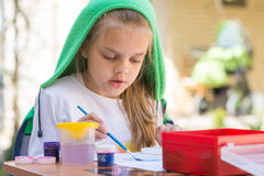 Girl draws paints in yard in the spring sunny day Royalty Free Stock Images