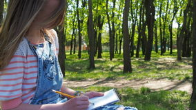 Girl draws in the park. A teenage girl on nature. Beautiful girl in denim overalls draws. stock footage