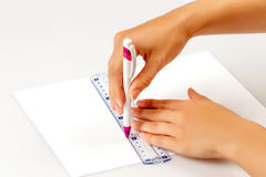 Girl draws a pen on a ruler on paper Royalty Free Stock Photo