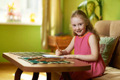 Girl draws pencil on paper at table. Girl draws pencil on paper at the table stock photo