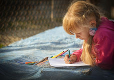 Girl draws a pencil on white paper. Stock Photo
