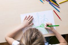 A girl draws with pencils a green house planet car wind power plants. Concept of ecology and environmental protection. stock images