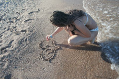 The girl draws on sand Stock Images