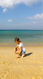 Girl draws in the sand on the beach. Thailand Stock Photo