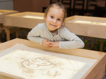 Girl draws with sand on a light table Stock Photography