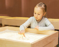 Girl draws with sand on a light table Royalty Free Stock Photos