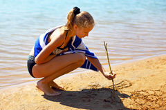 The girl draws on sea sand Stock Photography