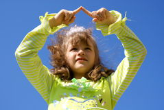 The girl draws in the sky fingers. The girl in green blouse draws in the dark blue sky fingers having lifted upwards hands Royalty Free Stock Photography