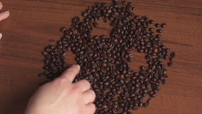 Girl draws a smiley face made of coffee beans stock video footage