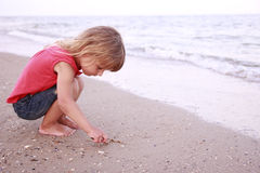 Girl draws a sun in the sand on the beach Royalty Free Stock Image