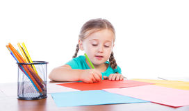 Girl draws at the table. On a white background Stock Photos