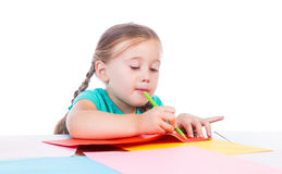 Girl draws at the table. On a white background Royalty Free Stock Photos