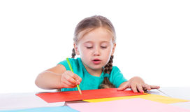 Girl draws at the table. On a white background Stock Image