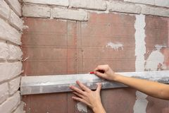The girl draws on the wall of the line for the exact location of bricks. The girl draws on the wall of the line for the exact location of  bricks royalty free stock photo
