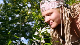 Girl with dreadlocked smelling a flower. HD stock footage