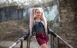 A girl with dreadlocks in a leather jacket and a short skirt stands against the background of an old stone wall. Sexy blond girl with dreadlocks in a leather Stock Images