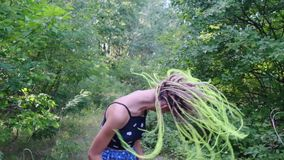 Girl with dreadlocks shakes her head. In the park in slow mo stock video footage