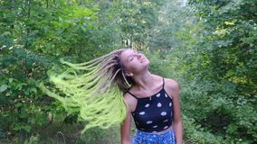 Girl with dreadlocks shakes her head. In the park in slow mo stock footage