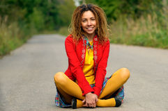 Girl with dreadlocks sits on asphalt Stock Photo