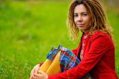 Girl with dreadlocks sits on grass. Young woman in red jacket, checkered skirt and yellow stockings Stock Images