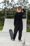 Girl with dreadlocks and a skateboard Stock Photo