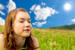 Girl dreamin on a meadow. Young woman lying on a meadow in summer Royalty Free Stock Photo