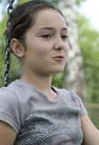 Girl dreaming. Brunette young girl on swing daydreaming royalty free stock images