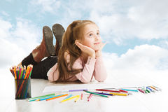 Girl dreaming, looking for drawing idea. Inspiration and creativity. Girl dreaming, looking for drawing idea. Smiling child lying over blue cloudy sky stock photos