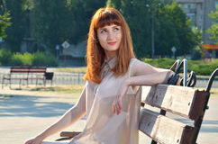 Girl dreaming sitting on a bench. Girl brown hair looks up sitting on the bench Stock Photos