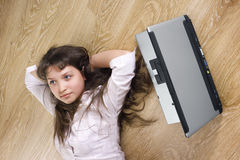 The girl dreams. Girl lies on floor, nearby the laptop Stock Photo