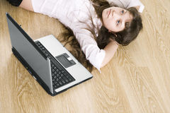 The girl dreams. Girl lies on floor, nearby the laptop Royalty Free Stock Image