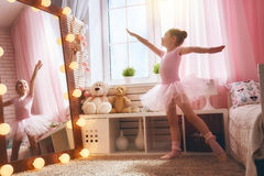 Girl dreams of becoming a ballerina. Cute little girl dreams of becoming a ballerina. Child in a pink tutu dancing in a kids room Royalty Free Stock Photo