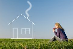 Girl dreams of the house. Girl in the field smells a bunch of flowers and dreams of the house Royalty Free Stock Photos