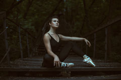 Girl dreams with pointe shoes. Girl sitting in the park at night and dreams of ballet in her legs pointe Royalty Free Stock Photos