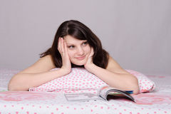 Girl dreams reading a magazine in bed Stock Photography