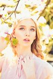 Girl on dreamy face, tender blonde near magnolia flowers, nature background. Lady walks in park on sunny spring day royalty free stock photos