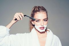 Girl on dreamy face wears bathrobe, grey background. Lady play with sharp blade of straight razor. Woman with face. Covered with foam holds straight razor in stock photos