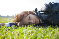 Girl with a dreamy look lying on the fresh spring. Photo of a girl with a dreamy look lying on the fresh spring grass Stock Image