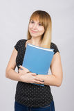 Girl with dreamy look standing with folders in hands Royalty Free Stock Photography