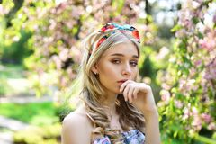 Girl on dreamy thoughtful face, tender blonde near sakura flowers, nature background. Spring bloom concept. Lady walks. In park on sunny spring day. Young woman royalty free stock images