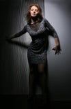 Girl in dress against dark background Stock Image