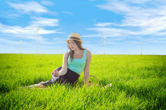 Girl in a dress and with an apple against the blue sky and wind generators royalty free stock photo