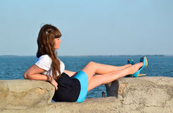 Girl in a dress on a background of the sea. Girl in a dress and shoes lying on the sea background Stock Photo