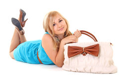 Girl in dress with bag lying on white Stock Images