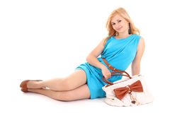 Girl in dress with bag sitting on white Stock Photo