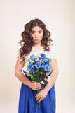 Girl in a dress with blue flowers in hands Royalty Free Stock Image