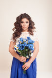Girl in a dress with blue flowers in hands Royalty Free Stock Photography