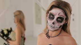 Girl in dress with a bouquet of black flowers and makeup in the form of skeleton. A young blonde in a black dress with a bouquet of black flowers and makeup in stock video